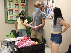 UNC Flourish Volunteer Shruti Temkar, Nutrition Education Chair Malik Tiedt, and Co-Director Sylvia Wang prepare to serve food at the SHAC Clinic in Carrboro on Sept. 29.