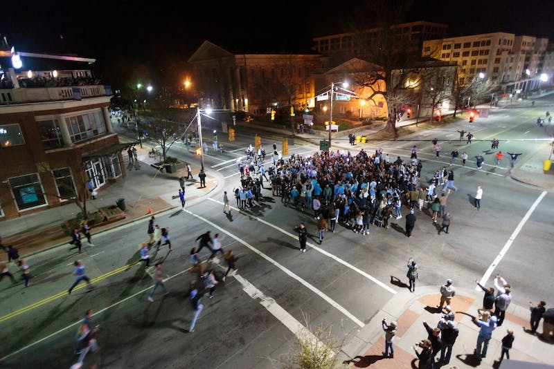 Fans run to the intersection of Franklin Street and Columbia Street to celebrate the Tar Heels' win over Duke.