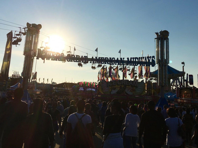 A crowd moves through the NC State Fair.