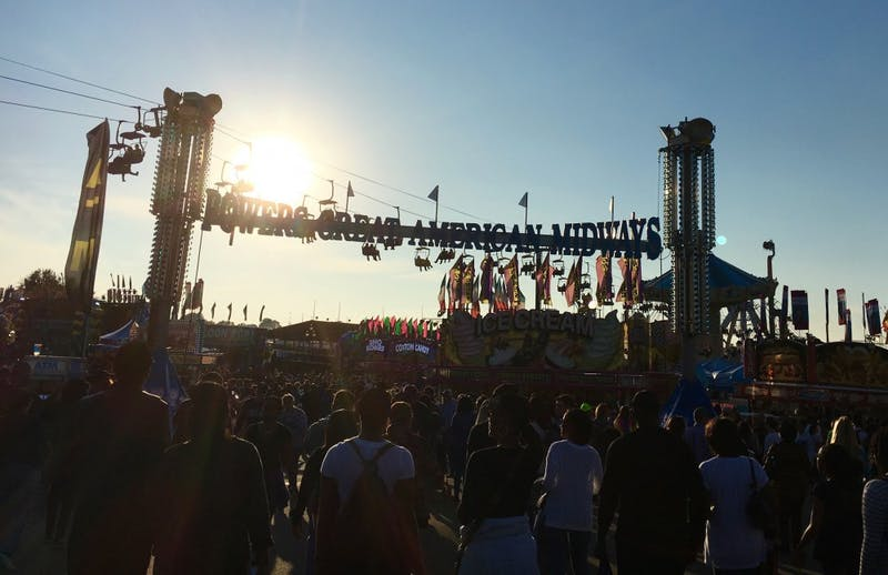 A crowd moves through the NC State Fair.