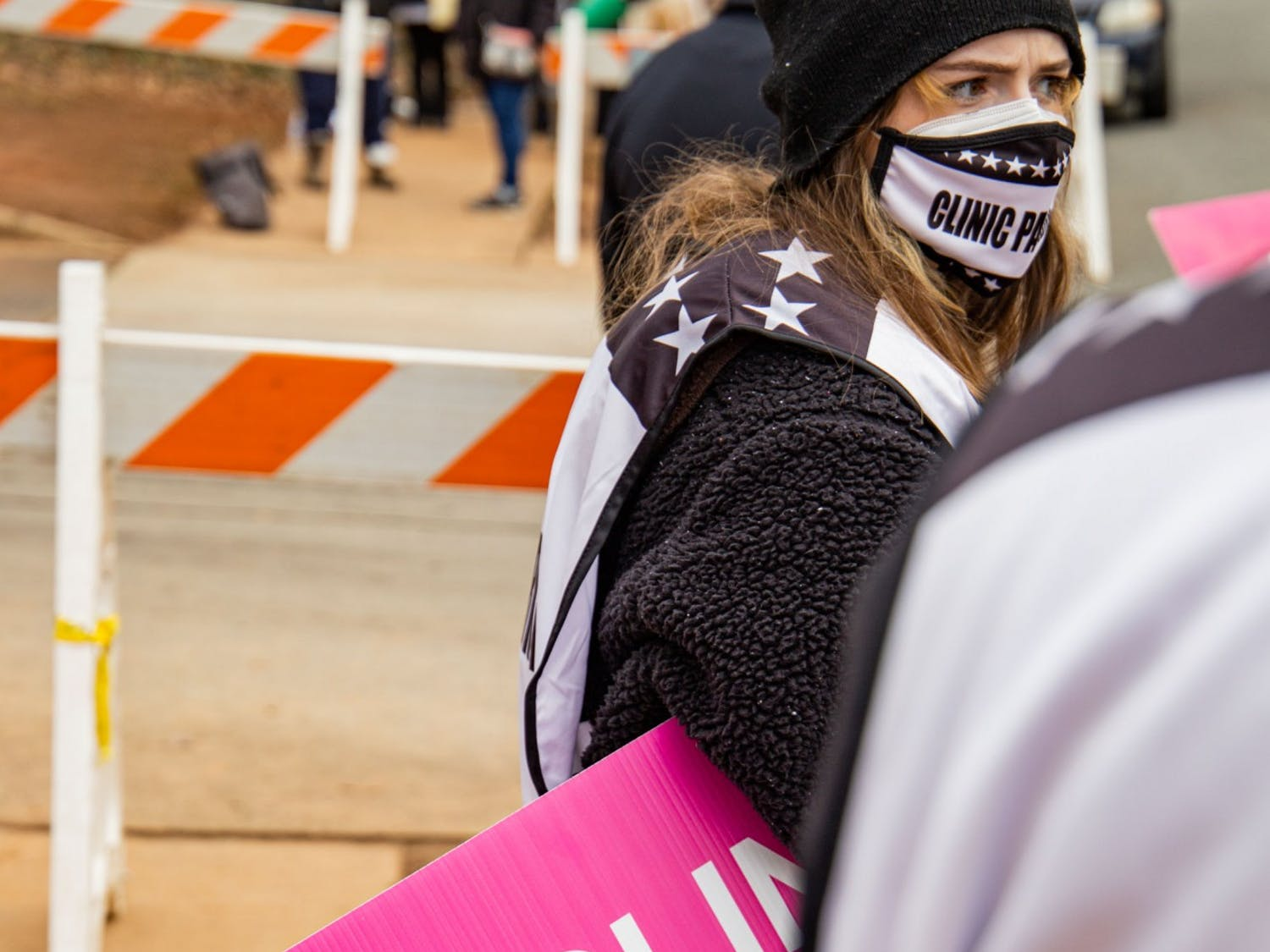 UNC student Reiley Baker stands among other volunteers at A Preferred Women's Health Center of Charlotte, only a few yards from the group of evangelical, anti-abortion activists who protest daily outside the clinic.