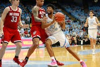 Sophomore K.J. Smith (30) drives past N.C. State players during game in early February. UNC men's basketball beat NC state with the most points scored on the Wolfpack since 2003. UNC won 113-96 at the Smith Center on Tuesday, Feb. 5, 2019