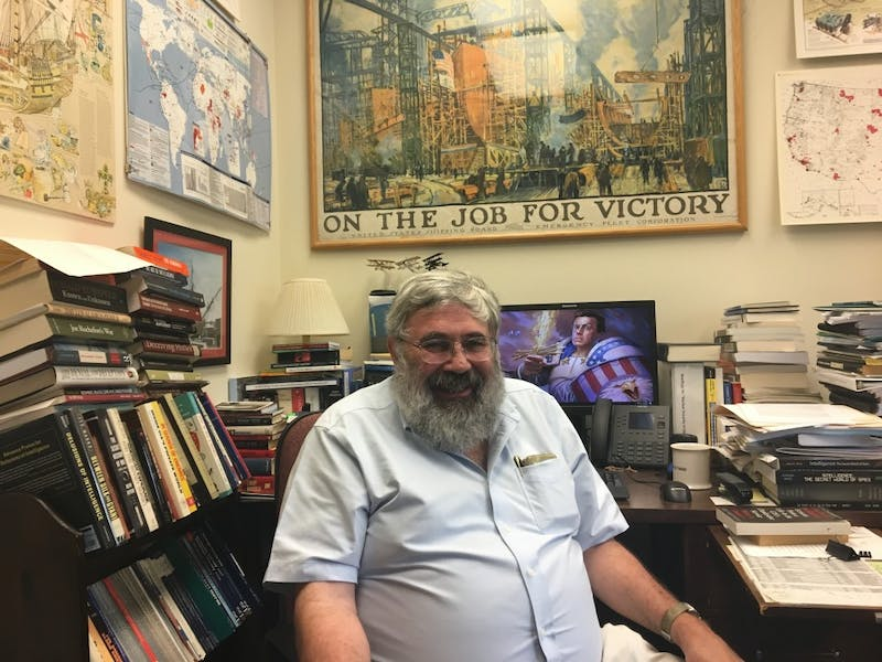 Joseph Caddell, a visiting lecturer in the History department, sits in his office — which is brimming with books and posters.