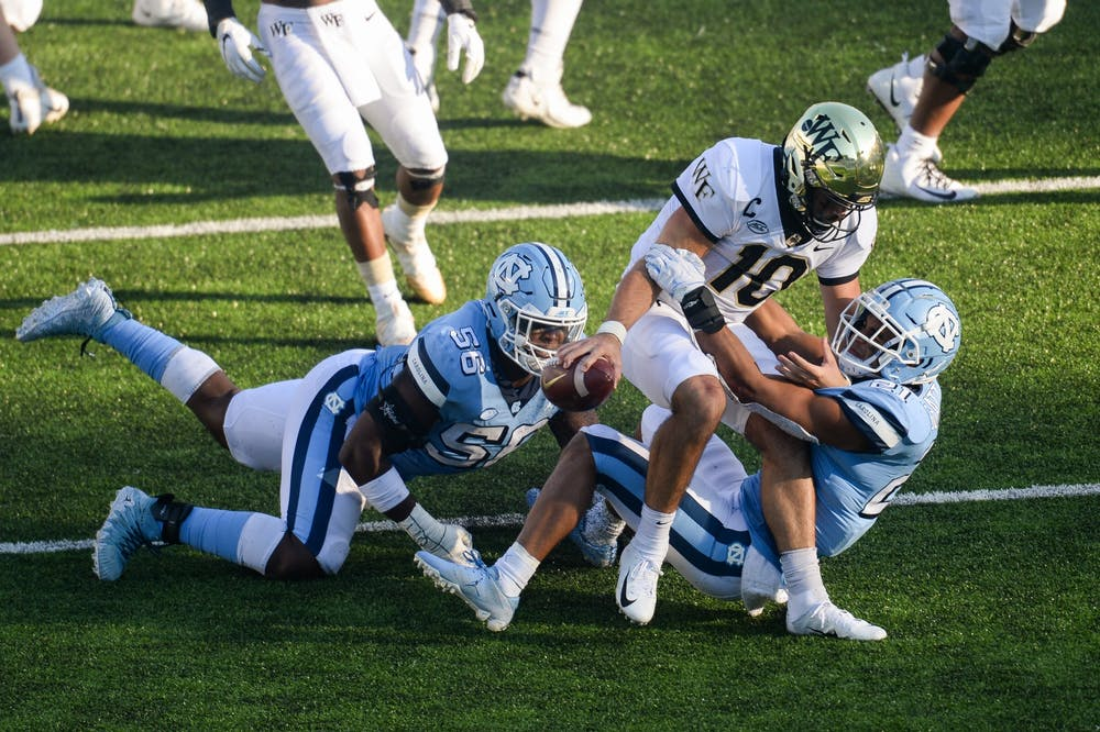 Wake Forest's redshirt sophomore quarterback Sam Hartman (10) is sacked by UNC's graduate linebacker Chazz Surratt (21) and sophomore defensive lineman Tomari Fox (56) during a game in Kenan Memorial Stadium on Saturday, Nov. 14, 2020. UNC beat Wake Forest 59-53.