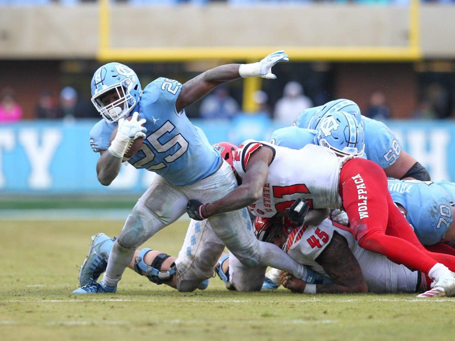 Running back Javonte Williams (25) tries to escape an NC State defender on Saturday, Nov. 24, 2018 in Kenan Memorial Stadium. NC State beat UNC 34-28 in overtime.