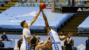 UNC first years Walker Kessler (13) and Day'Ron Sharpe (11) attempt to tip in the ball during a game against Marquette in the Smith Center on Wednesday, Feb. 24, 202. UNC lost to Marquette 83-70.