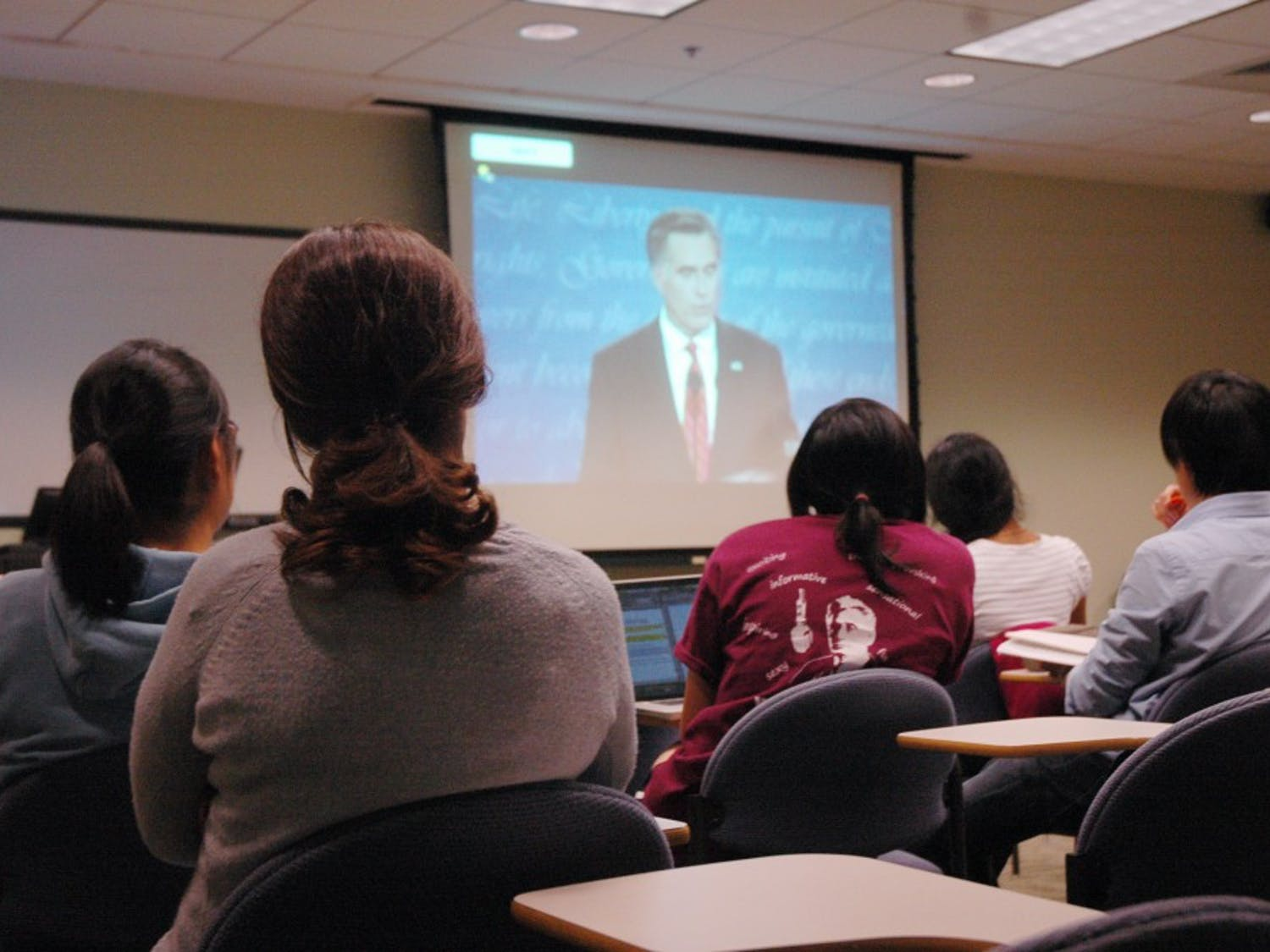 Freshman Dicle Kara, left, and other students watch the Presidential debate on Wednesday night in the Undergraduate Library.