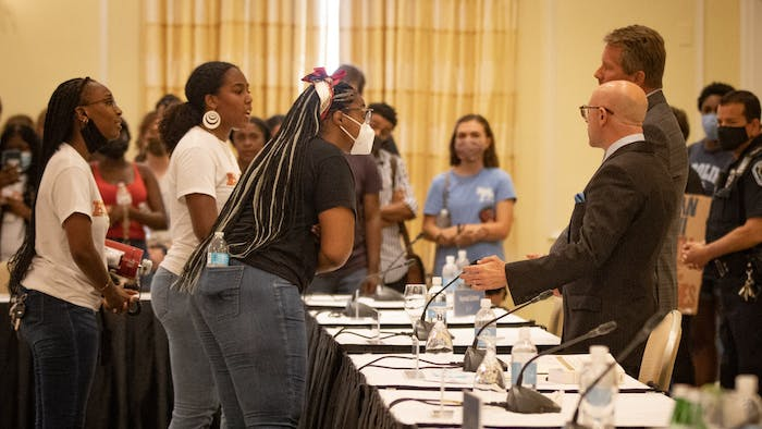 Student activists from the Black Student Movement speaks to Board of Trustees President Gene Davis and UNC Chancellor Kevin Guskiewicz after the BOT meeting that granted tenure to Nikole Hanna-Jones.