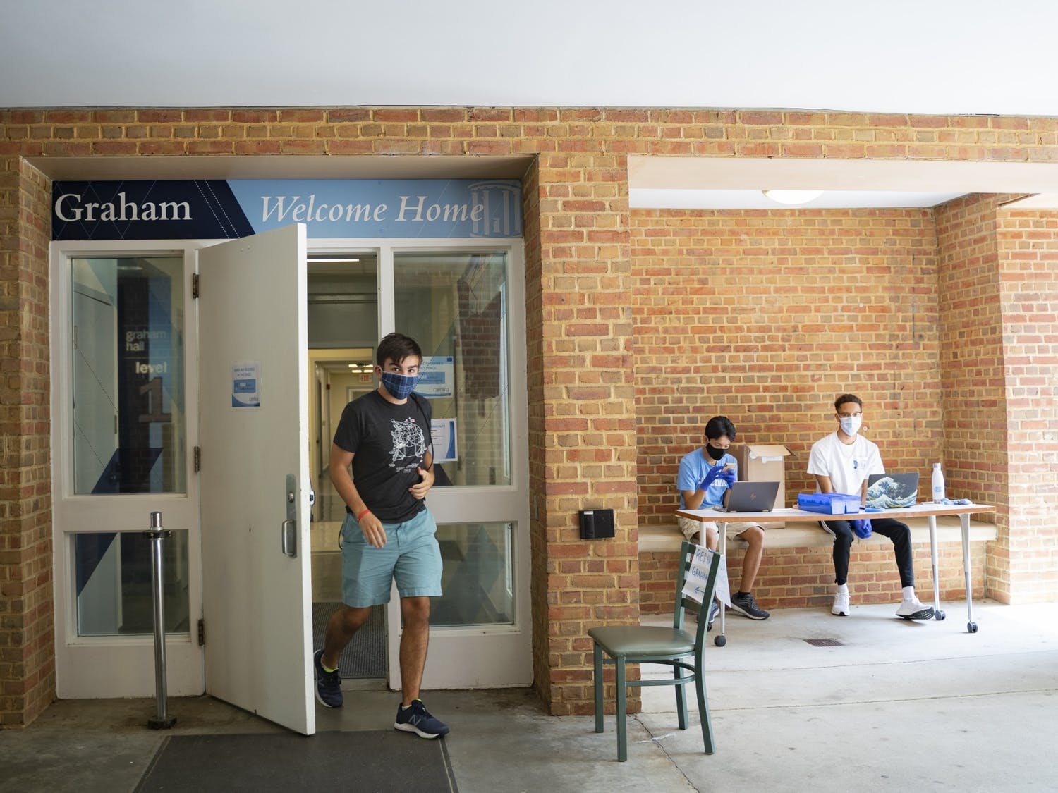 Tyler Smith, an incoming first-year, exits Graham Residence Hall wearing a mask as two RA's, sophomores Tiel Pham (left) and Nigel Goins (right) sit in the entryway to assist with move-in on Wednesday, Aug. 5, 2020.