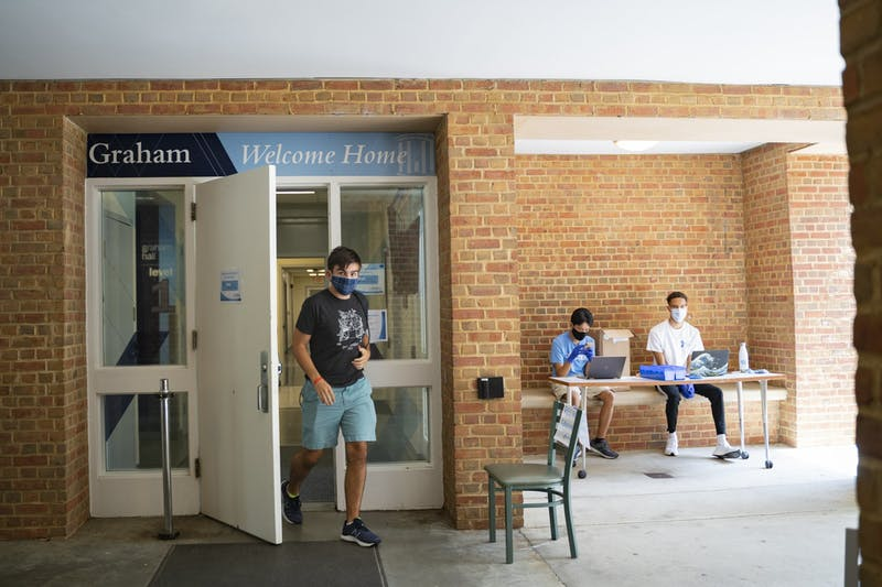 An incoming first-year exits Graham Residence Hall wearing a mask as two RA's, sophomores Tiel Pham (left) and Nigel Goins (right) sit in the entryway to assist with move-in on Wednesday, Aug. 5, 2020.