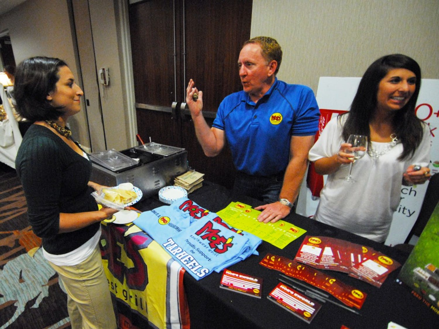 The Chapel Hill Chamber of Commerce Expo was held at the Sheraton Hotel in Chapel Hill. New Chamber members as well as returning members showcased their businesses. Kevin Rutledge and Becca Thomas of Moe's Southwest Grill in Durham share chips and queso with Samantha Handler of Aflac. Both companies were in attendance at the Chapel Hill Chamber of Commerce Expo.