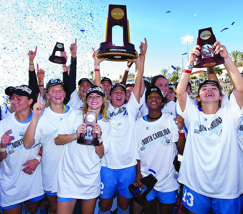 Amber Brooks holds up the NCAA Championship trophy while celebrating with her teammates after winnin the 2012 NCAA Championship.