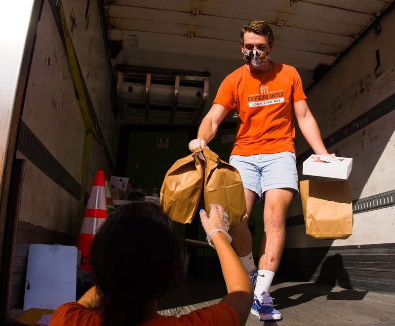 Manfred Franz walks out of the refrigerated truck with a Carrboro United customer's orders on Saturday, Oct. 24, 2020.