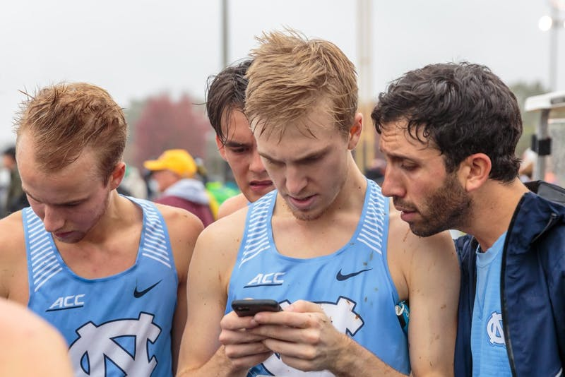 (From left) Alex Milligan, Mitch Resor, Jeremy Brown, and assistant coach Bobby Lockhart look at the race results after the men's 10k during the NCAA Southeast Regional Championships at Winthrop University in Rock Hill, SC on Friday, Nov. 9 2018.