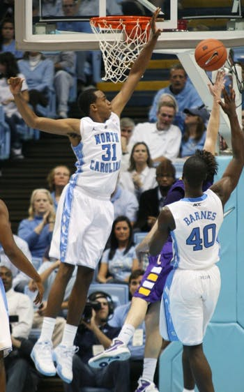 Freshman Harrison Barnes (40) scores two of his 14 points in his debut as a Tar Heel. John Henson (31), blocking above, was just three swats away from recording a triple-double.