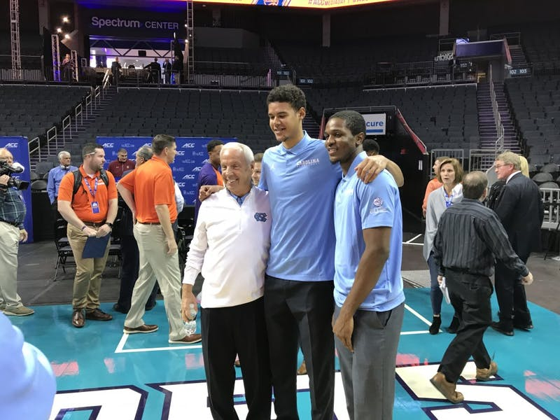 UNC men's basketball head coach Roy Williams and guards Cam Johnson and Kenny Williams pose for a picture at the Spectrum Center for ACC men's basketball media day on Oct. 24.