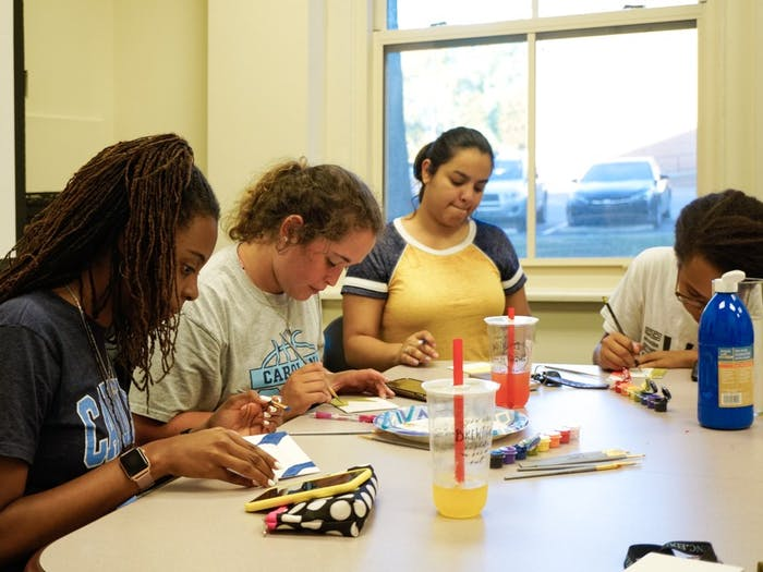 """On September 23rd at the Carolina Latinx Center, students (left to right) Jadah Smith, Isabella Lima, Elena Delvalle, and Bianca Goodwin participate in """"Paint My Latinidad"""" by each painting a visual representation of their latinidad. This event was one of many hosted by the Carolina Latinx Center as a way to celebrate Latin Heritage Month and raise conversations about Latinx culture."""