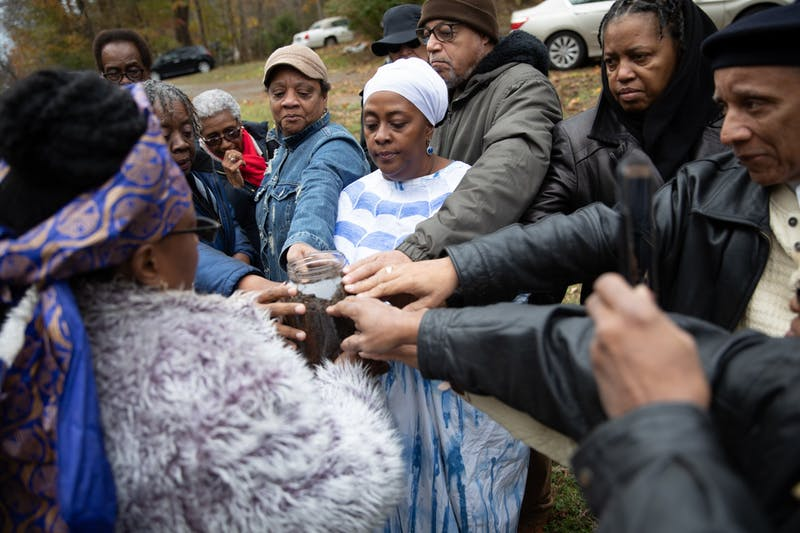 "Danita Mason-Hogans (center), 52, of Durham, and other descendents of Manly McCauley gather to place their hands on a jar containing soil during a soil collection ceremony at Carl Drive in Chapel Hill, N.C., on Satuday, Nov. 16, 2019. ""I always say that I'm doing the work of my ancestors,"" says Mason-Hogans. ""We need to be brave together and face it together."""