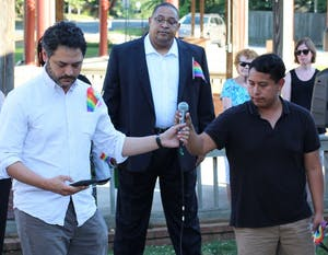 Mark Kleinschmidt reads names of Orlando shooting victims alongside Winston Crisp and Emilio Vicente at a vigil in Carrboro.
