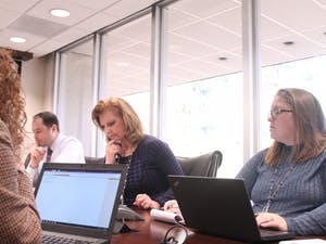 Ed Purchase (left), Lynne Sanders (center) and Heather Hummer (right) discuss logistics of their yearly conference at C.D. Spangler Building in Chapel Hill, NC on the morning of Thursday, Jan. 10, 2019.