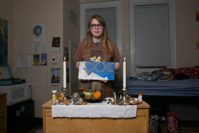 Emily Lewis, a sophomore studio art major, poses at her altar holding a painting of the Goddess she created herself. Lewis converted to Wicca this past summer and is incoporating her spirituality into her everyday life.