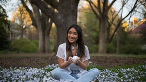 Junior Advertising and Public Relations major Tran Nguyen holds her bowl of crystals in the Coker Arboretum on Thursday, Apr. 1, 2021.
