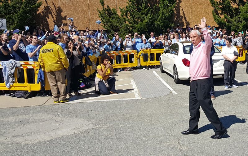 Coach Roy Williams waves at the crowd after UNC men's basketball returned from Houston on Tuesday.