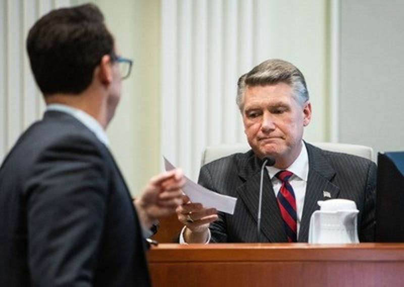 Josh Lawson, chief counsel for the state Board of Elections and Ethics Enforcement, left, hands Mark Harris, Republican candidate in North Carolina's 9th Congressional race, a document during the fourth day of a public evidentiary hearing on the 9th district's voting irregularities investigation on Thursday, Feb. 21, 2019, at the North Carolina State Bar in Raleigh, N.C. (Travis Long/Raleigh News & Observer/TNS)