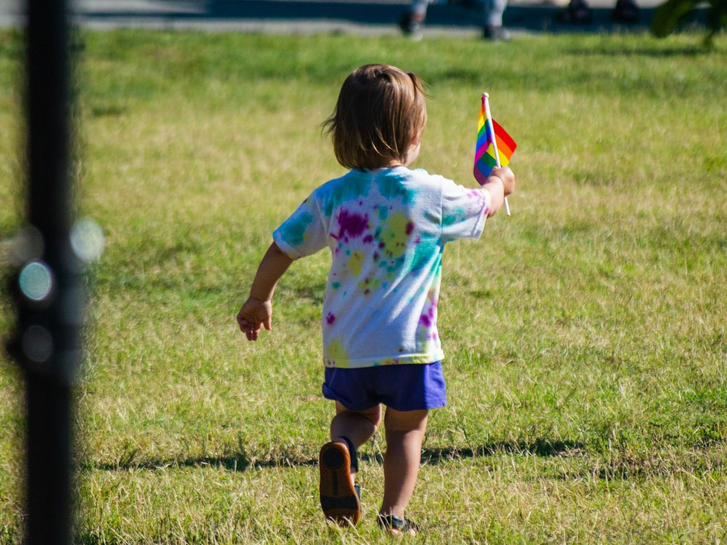 A child runs with a rainbow flag at the Chapel Hill Carrboro Small Town Pride Food Truck Rodeo and Dance Party in Carrboro on Thursday June 24, 2021.