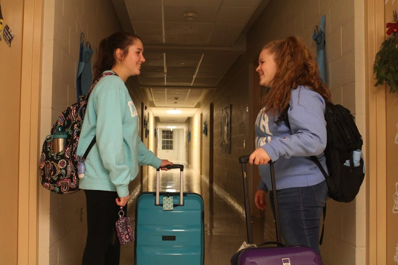 DTH Photo Illustration. UNC sophomores Lindsey Cole (left), psychology major, and Hillary Jacobs (right), applied math major, prepare their suitcases to leave Craige Residence Hall  on Wednesday, Nov. 28, 2018.
