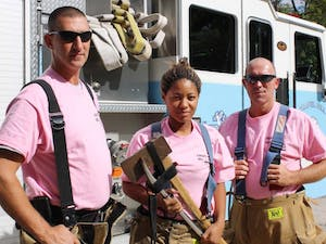 Captain Robbie Borgesi, Ashley Brooks, firefighter, and David Park, fire equipment operator, of Chapel Hill Fire Department -- Station 1 sport pink undershirts as part of their uniform during Breast Cancer Awareness Month.