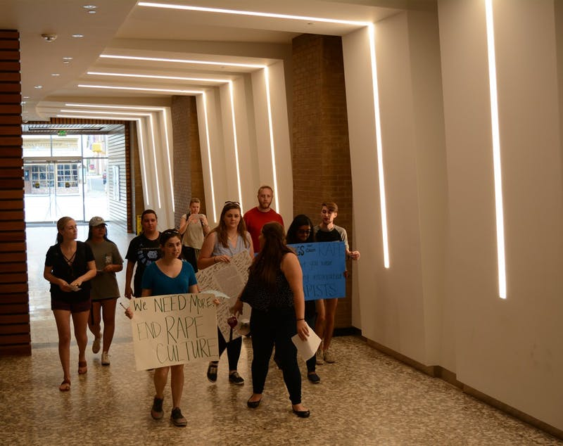 Protesters march down the hallway leading to the location of the Equal Opportunity and Compliance Office.