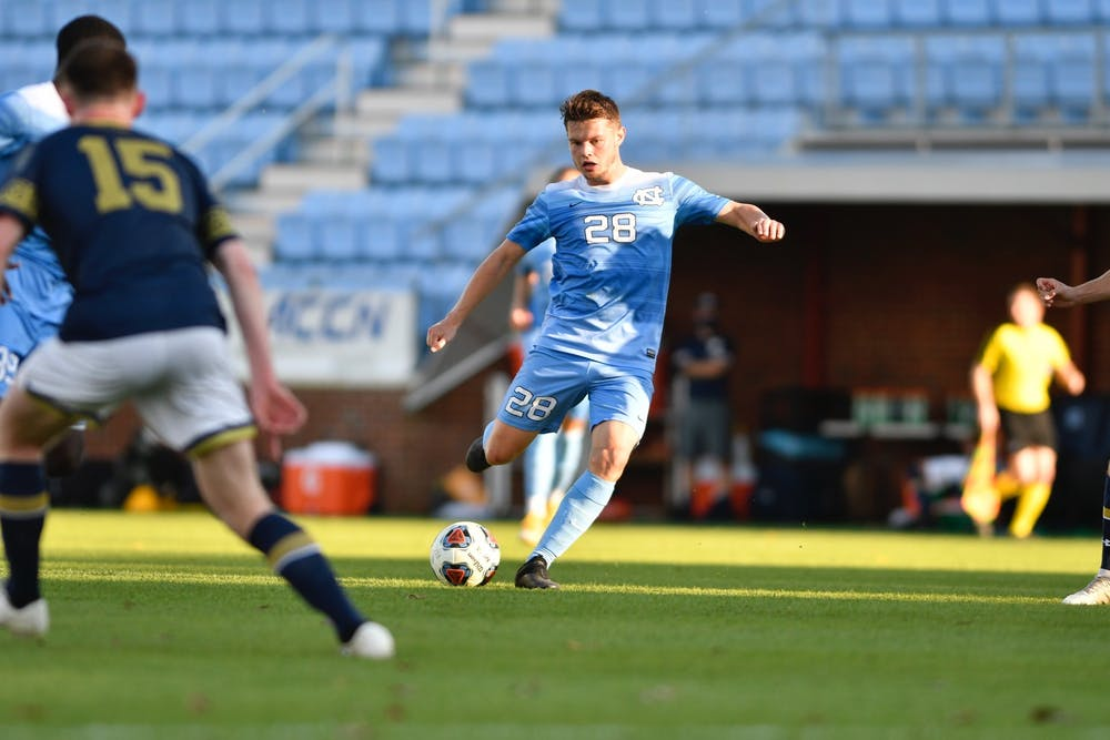 <p>UNC's first year midfielder Tim Schels (28) kicks the ball during the first round of the ACC tournament against Notre Dame in Dorrance Field on Sunday, Nov. 15, 2020. UNC fell to Notre Dame 1-0. Photo courtesy of Dana Gentry for UNC Athletic Communications.&nbsp;</p>