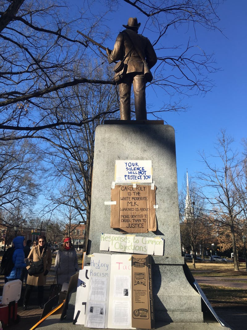 Signs taped to the base of Silent Sam in January 2018 reproached University administrators for their actions regarding the Confederate memorial.