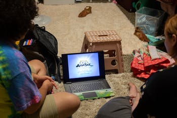 DTH Photo Illustration. Two people watch Avatar: the Last Airbender on a laptop.