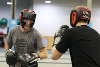 UNC club boxing coach Josh Sokal (left) practices sparring with a student in the Eddie Smith Field House on Friday evening.