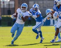 Running back Michael Carter (8) outruns Duke safety Jeremy McDuffie (9) at Wallace Wade Stadium on Nov. 10, 2018.