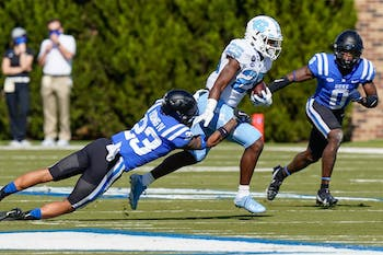 UNC running back Javonte Williams (25) runs for yardage tackled by Duke safety Lummie Young IV (23) and safety Marquis Waters (0) during the first quarter at Wallace Wade Stadium. Photo courtesy of Jim Dedmon-USA TODAY Sports