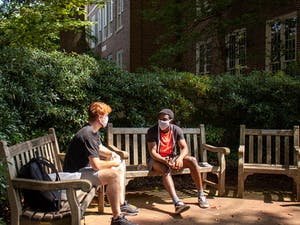 Two students wearing masks chat on the benches outside of Carolina Hall on Tuesday, Sept. 15, 2020.