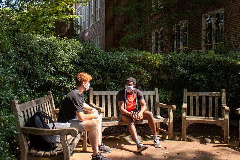 Two students wearing masks chat on the benches outside of Carolina  Hall on Tuesday, Sept. 15, 2020