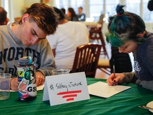 (From left to right) Sergio Jimanez, senior at Chapel Hill High School and Jasper Cobb, senior at Middle College High School at Durham Technical Community College, write letters to  Kanautica Zayre-Brown at the Queer Family Gathering dinner at a community building in Carrboro, Tuesday, March 19, 2019. Kanautica is a trans woman incarcerated at a men's prison and who has been in solitary confinement for 17 days. The letters are meant to help Kanautica maintain her mental health during her confinement until she can be moved into a women's facility.