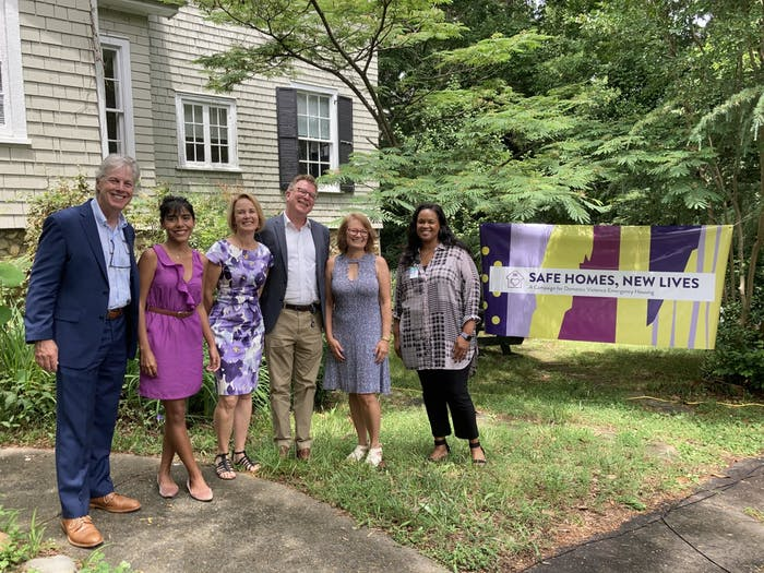 The speakers at the Safe Homes Celebration on June 4, 2021 gather for a photo. From left to right: Gary Bowen, PhD, Dean of UNC School of Social Work; Natalia Rivadenerya, Emergency Housing Coordinator, Compass Center for Women and Families; Gillian Hare, Board Chair, Compass Center for Women and Families; Martin Baucom, Vice-President for Development, UNC Health Foundation; Jeannie Denuo, Safe Homes Campaign Co-Chair and Compass Center Board Member; Loryn Clark, Deputy Town Manager for the Town of Chapel Hill. Photo courtesy of Ann Simpson/Compass Center.