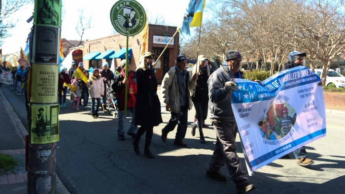 Demonstrators march on E. Main Street in Carrboro on Tuesday to protest the labor practices of Wendy's.