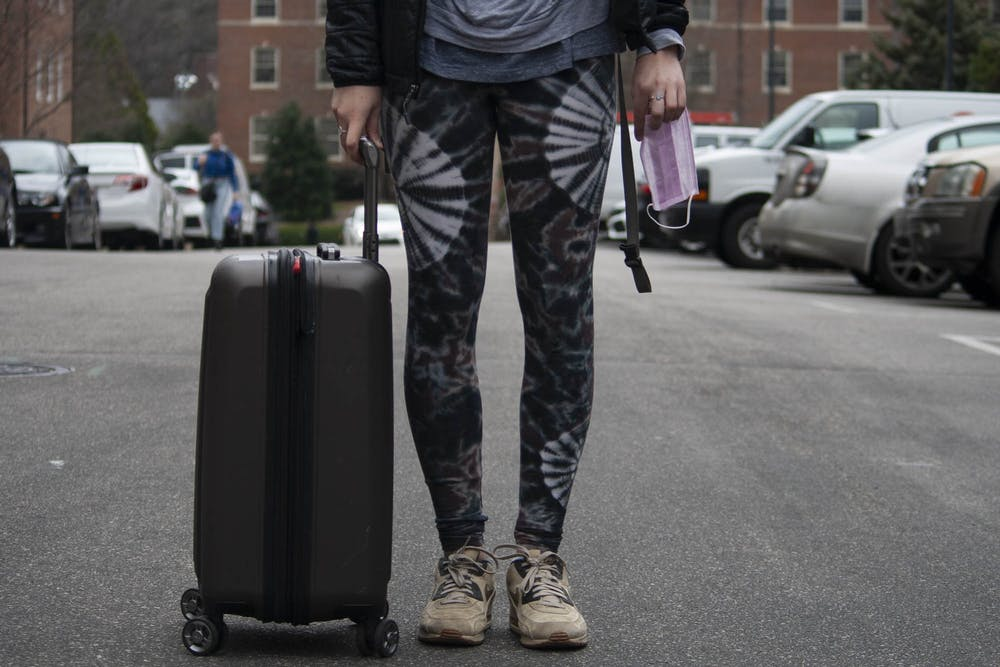 <p>DTH Photo Illustration. A UNC student holds a suitcase and a surgical mask on campus on Tuesday, March 3, 2020. The coronavirus has cancelled various study abroad programs.&nbsp;</p>