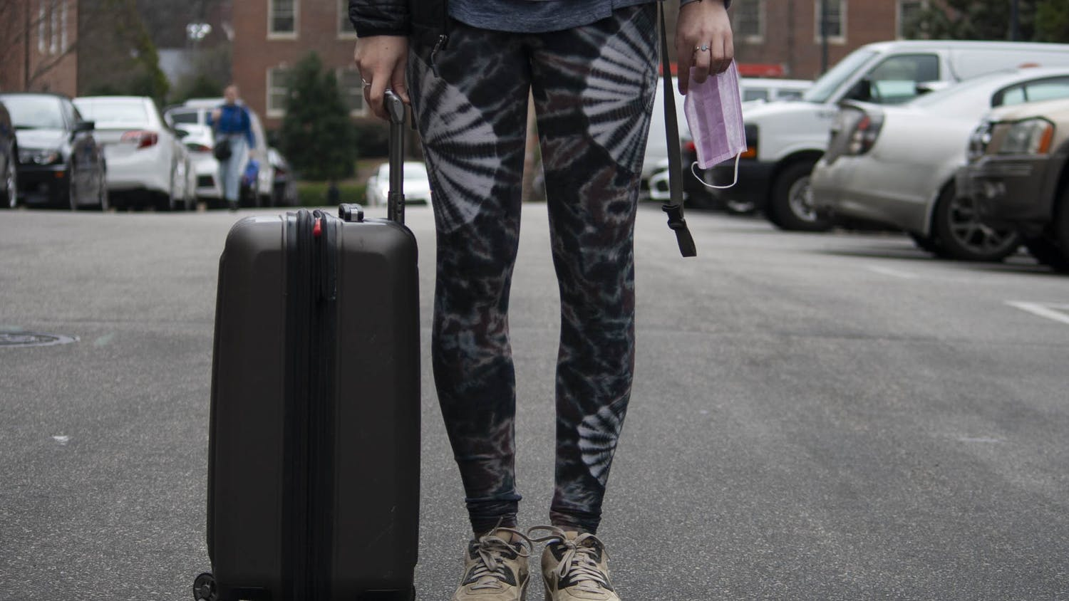 DTH Photo Illustration. A UNC student holds a suitcase and a surgical mask on campus on Tuesday, March 3, 2020. The coronavirus has cancelled various study abroad programs.