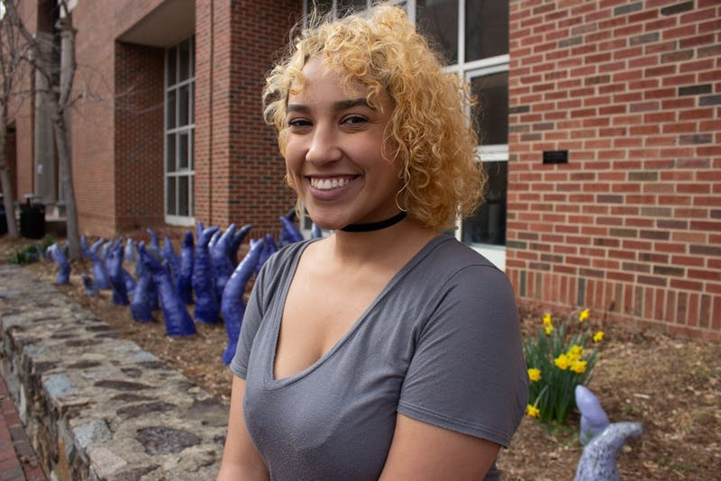 """Noni Shemenski, a communications studies major, will host Out Loud: POC Art Market & Variety Show, which is hosted by HERE: Representation in Arts & Comedy Festival. The event will include performances, art, standup, poetry and music by people of color.  Shemenski wants to host the show because """"it's important to showcase the variety of talents that people of color on campus have that often go unseen or unappreciated."""" The event will take place on Saturday, Feb.23, 2019 at The PIT Chapel Hill."""