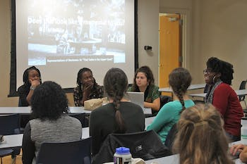 """Students gather in Saunders Hall for """"Representations of Blackness: That Table on the Upper Quad,"""" a roundtable discussion on campus memorials."""