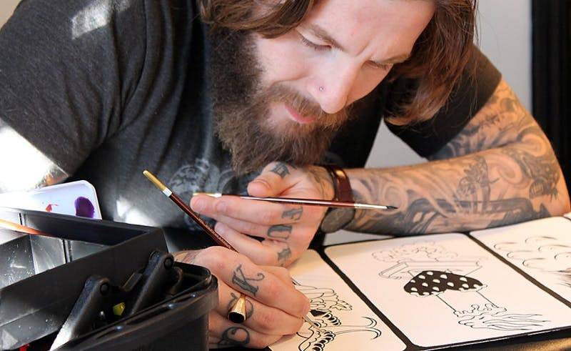 Mike Wheeler, an artist at Ascension Tattoo on Franklin Street, prepares tattoo stencils.