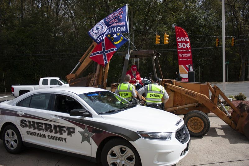 The Chatham County Sheriff's office pulls over a man driving a backhoe at a protest in Pittsboro on Saturday, Oct. 19, 2019.