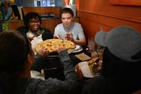 Brooklyn Pierson (right), a junior media and journalism major, takes a slice of pizza during a dinner with friends from her ministry on Nov. 8, 2018, at the Mellow Mushroom. Pierson is the organizer of a Friendsgiving planned for the following week.